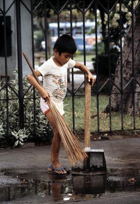 Nuori poika siivoamassa katukivetystä Manilassa. Kuva: UN Photo/Jean Pierre Laffont